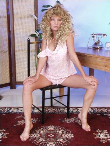 Mooie blonde krullebol doet poseren in haar nachtjurk waar ze in slaapt